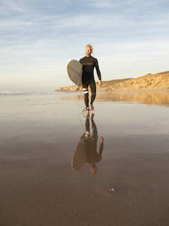 Man carrying surfboard while walking with reflection on beach against sky - KBF00640