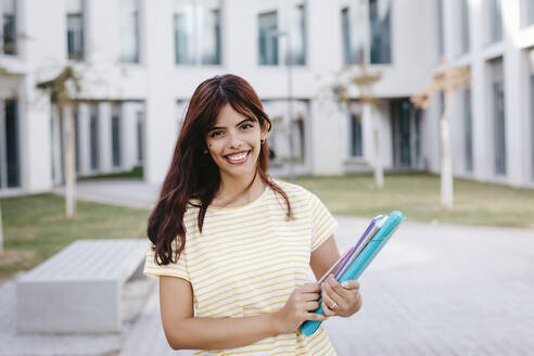 Smiling young woman student at university campus - TCEF01364