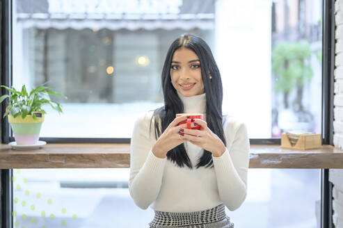 Smiling businesswoman holding cup of coffee against window in cafe - PGF00236