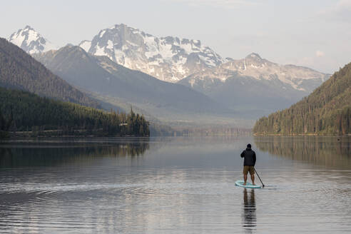 Back view of anonymous male on paddleboard on calm surface of Duffey lake and enjoying landscape of mountains in morning in British Columbia - CAVF90872