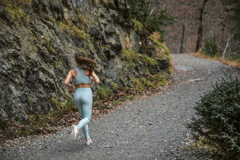 Young woman exercising while running on forest path - ACPF00921