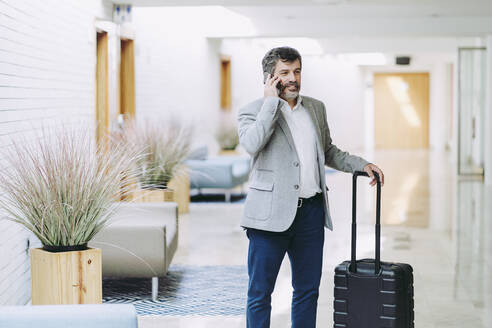 Businessman on phone standing with wheeled luggage in hotel corridor - DGOF01765