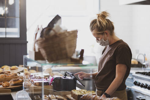 Waitress wearing face mask working in a cafe. - MINF15451