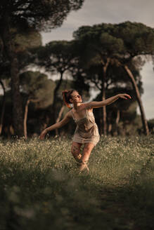 Tranquil female ballet dancer balancing barefoot on meadow in park in Iceland while performing with closed eyes and outstretched arms - ADSF17765
