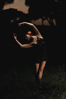 Elegant female ballet dancer in dress standing in meadow with raised arms and performing in dark park in Iceland - ADSF17777