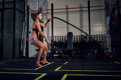 Side view of young strong muscular female athlete in activewear doing exercise on battle ropes during functional workout in modern gym - ADSF17804