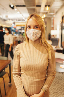Serious young female employee in casual outfit and protective mask looking at camera while standing against blurred interior of modern coworking space - ADSF17839