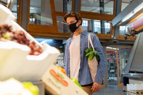 From below young male customer in protective mask carrying eco friendly recycled fabric shopping bag and choosing fresh groceries while buying food in supermarket - ADSF17923