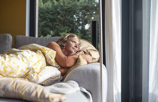 Thoughtful woman looking through window while lying on sofa at home - BFRF02309