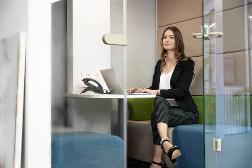 Confident businesswoman using laptop while sitting in cabin at office - PESF02291