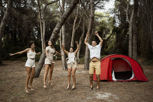 Cheerful family jumping in forest against at campsite during vacation - RCPF00330