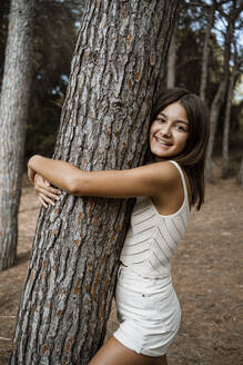 Smiling girl embracing tree trunk while standing in forest - RCPF00384