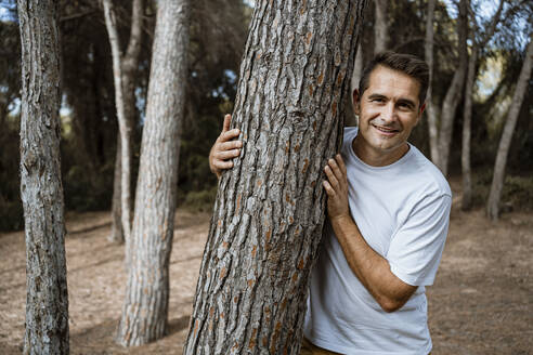 Smiling man embracing tree trunk in forest during vacation - RCPF00387