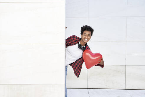 Happy young woman holding red heart shape balloon while standing behind white wall - VEGF03160