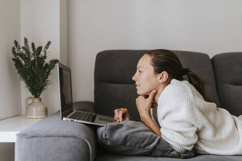 Woman using laptop while lying on sofa in living room - DMGF00327