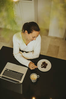 Woman eating chocolate brownie while sitting laptop and coffee at kitchen island - DMGF00345