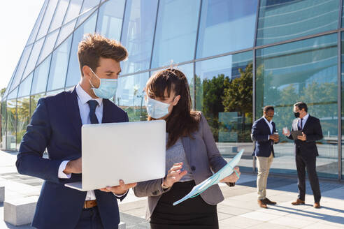 Unrecognizable young man and woman in formal suits and medical masks examining documents while working together on street using laptop near modern business building - ADSF18079