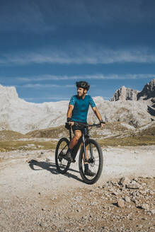 Cyclist with bicycle exploring Picos de Europa National Park on sunny day, Cantabria, Spain - DMGF00352