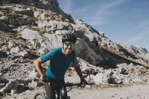 Cheerful male cyclist on bicycle against mountain during sunny day, Picos de Europa National Park, Cantabria, Spain - DMGF00373