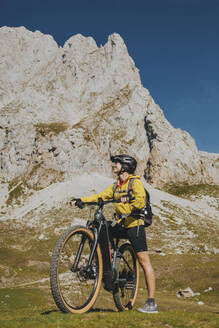 Female cyclist with bicycle against rock mountain at Picos de Europa National Park, Cantabria, Spain - DMGF00376