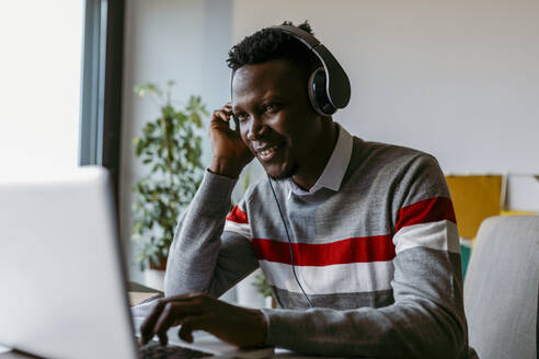 Smiling male entrepreneur with headphones using laptop at home - VABF04087
