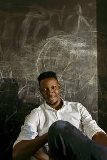 Smiling male entrepreneur sitting against scribble wall - VABF04114
