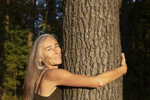 Smiling woman with long gray hair hugging tree at park - FCF01930