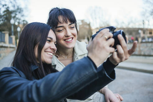 Smiling woman standing by female friend taking photograph with DSLR camera - MGRF00066