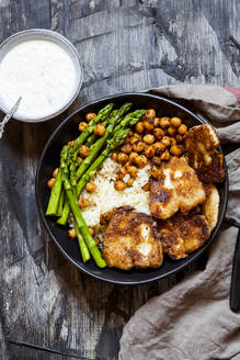 Dipping sauce and bowl of rice with chick-peas, asparagus stalks and friedhalloumicheese - SBDF04433