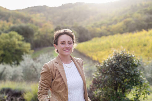 Businesswoman standing in vineyard during autumn - EIF00348
