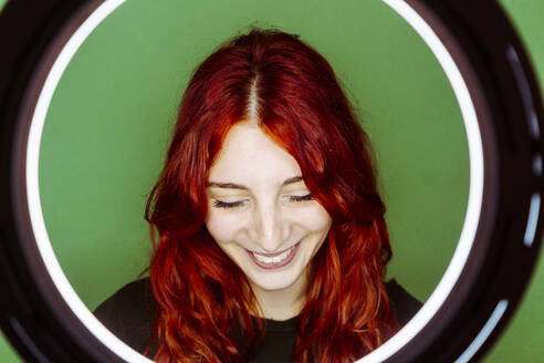 Smiling redhead woman with ring flash light standing against green background - GIOF09900