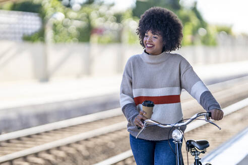 Thoughtful young woman with reusable cup wheeling bicycle at station - GGGF00235