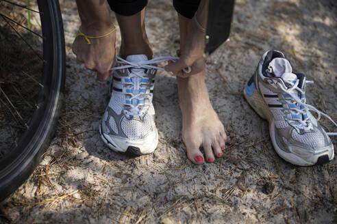 Female athlete tying sports shoelace by tire - CHPF00711