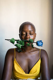 Woman closing eyes while sitting with blue rose in mouth against wall at home - RCPF00460