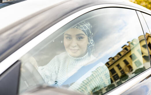 Young woman smiling while sitting in car - JCCMF00068