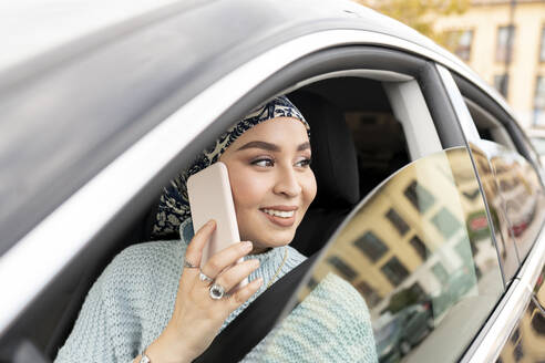 Young woman talking on mobile phone while sitting in car at city - JCCMF00071