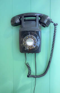 Vintage rotary landline phone hanging on turquoise wooden wall at barber shop - AJOF00753