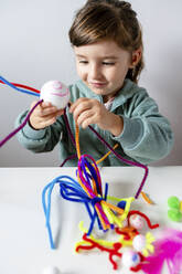 Smiling girl making toys of styrofoam ball and pipe cleaners while sitting at home - GEMF04427