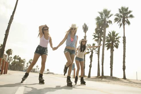 Happy female friends roller skating by beach against clear sky on weekend - AJOF00762