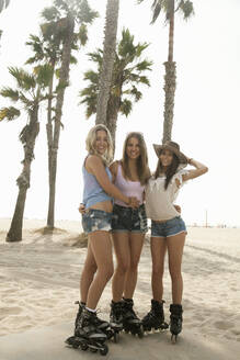 Smiling female friends on inline skates at beach during vacations - AJOF00765