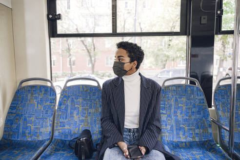 Young businesswoman traveling in bus during COVID-19 - VYF00285