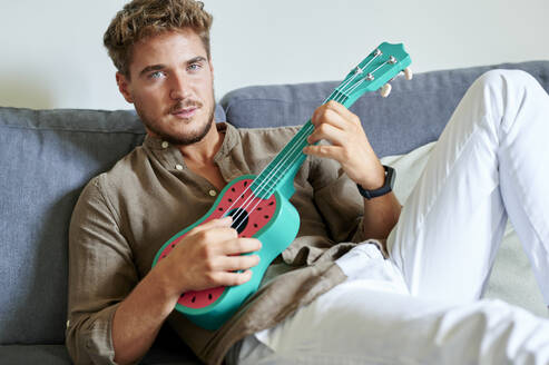 Young man learning ukulele while sitting on sofa in living room - KIJF03412