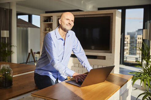 Smiling businessman looking away while using laptop sitting at home - FMKF06774