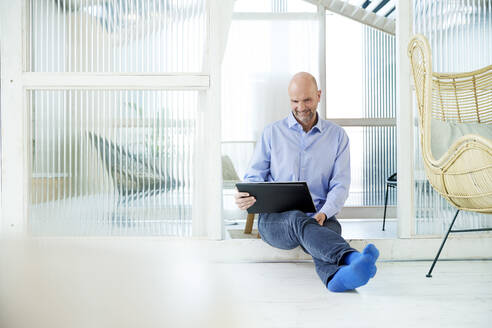 Mature businessman using laptop while sitting at home - FMKF06783