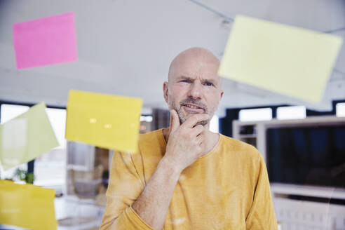 Confused man with hand on chin reading adhesive note - FMKF06804