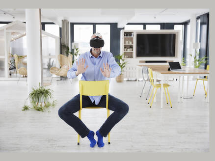 Mature businessman using virtual reality headset while sitting on chair at home office - FMKF06825