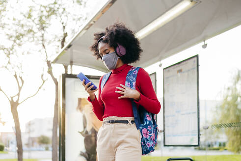 Young woman wearing headphones and protective face mask using smart phone while standing at bus stop - MARF00005