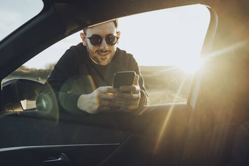Handsome young man using smart phone while leaning on car window during sunset - MTBF00729