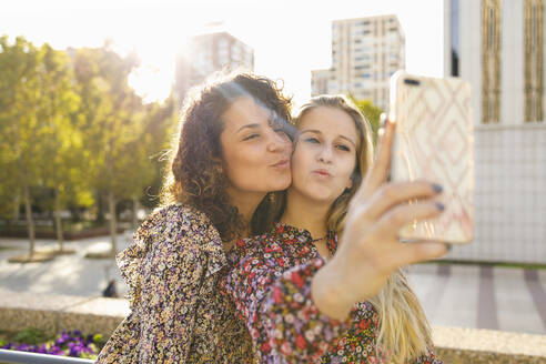 Female friends puckering while taking selfie through smart phone on sunny day - IFRF00139