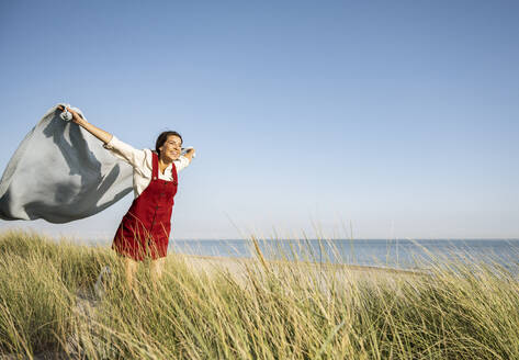 Young woman with arms outstretched holding shawl while standing at beach - UUF22230